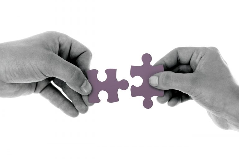 Two hands holding one jigsaw puzzle piece each